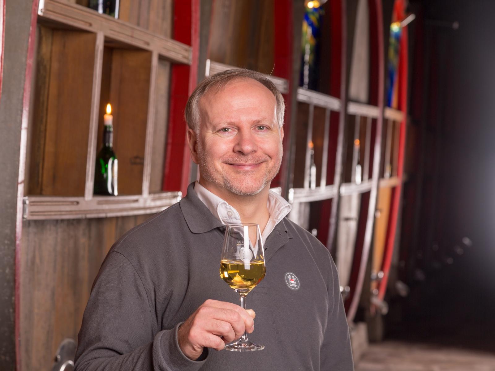 Portrait-Foto von Stephan Merz, dem Leiter des GWF Winzerkellers Hammelburg, vor Weinfässern im Gewölbekeller
