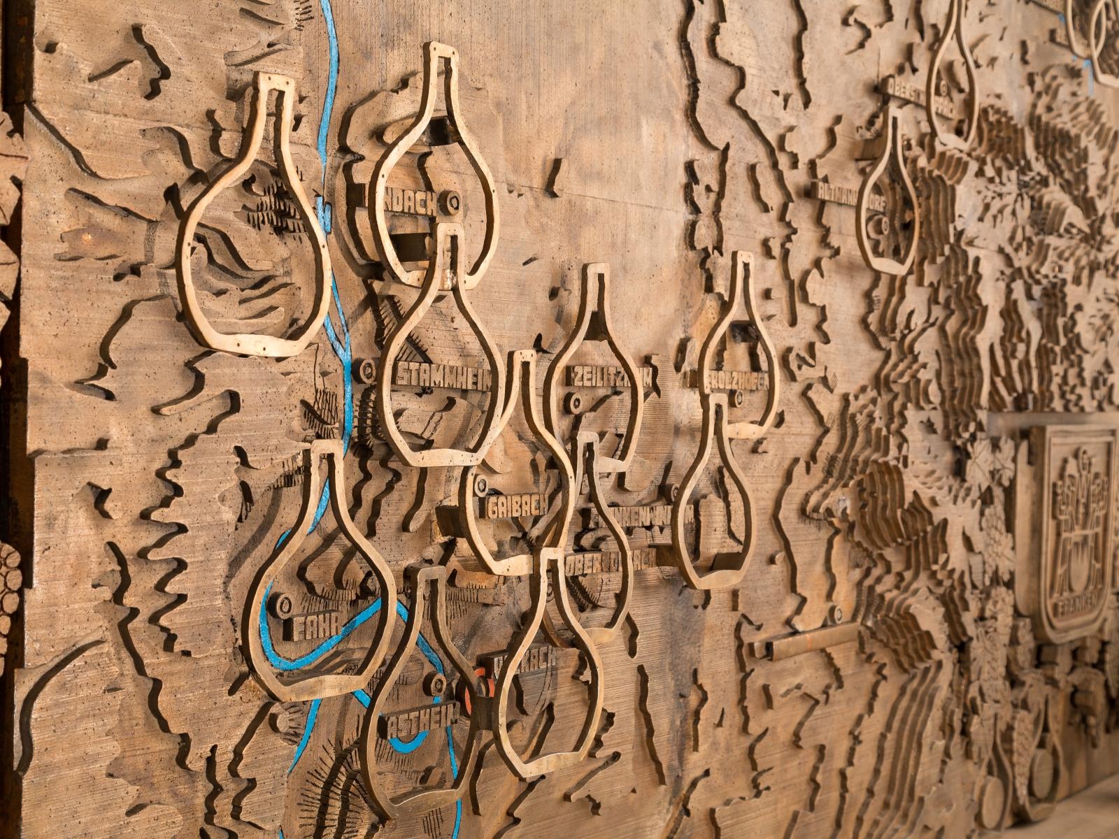 Nahaufnahme der zierlichen Kupferplatte, welche sich im Eingangsbereich der Vinothek befindet.
