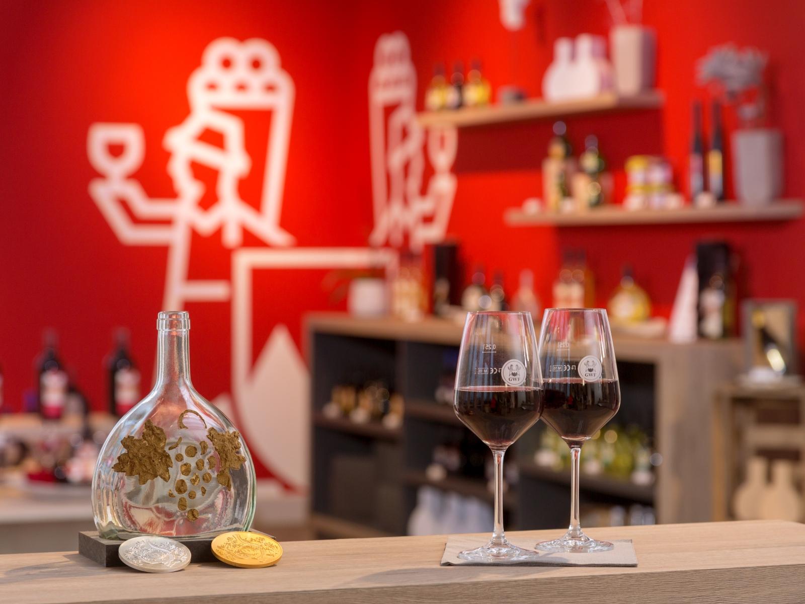 Ein Arrangement von eingeschenkten Weingläsern mit der GWF Mainschleifen Vinothek im Hintergrund.