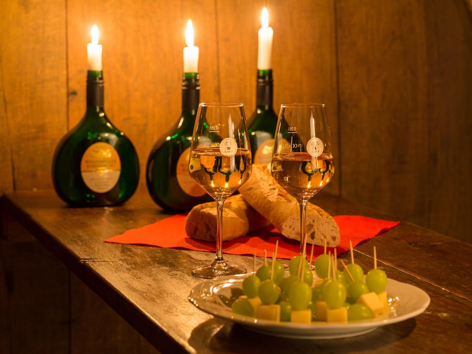 Gefüllte Weingläser sowie Brot und Käse-Traube-Häppchen mit Kerzen in Bocksbeuteln im Hintergrund