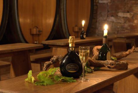 Sekt im Bockbeutel mit Sektglas vor den Weinfässern im Gewölbekeller